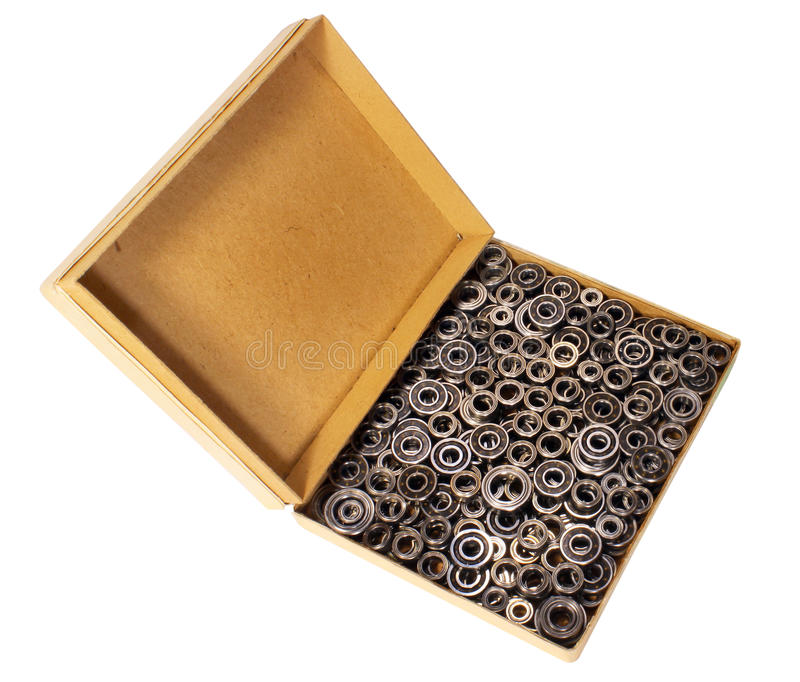 Old cardboard box with many small ball bearings isolated on whit. E background royalty free stock photo