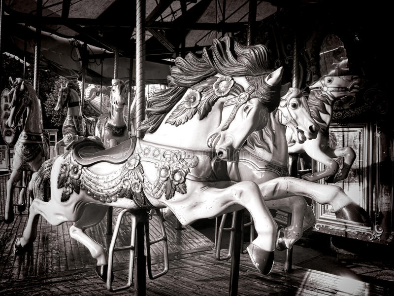 Old Carousel Horse Merry Go Round Amusement Ride. Antique style carved wood nostalgic carousel riding horse with vintage decorations on an old amusement merry go stock images