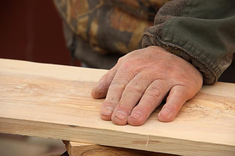 The old carpenter checks the quality of the sanding of the wood. A man`s hand strokes a wooden board. Making wooden furniture con royalty free stock photography