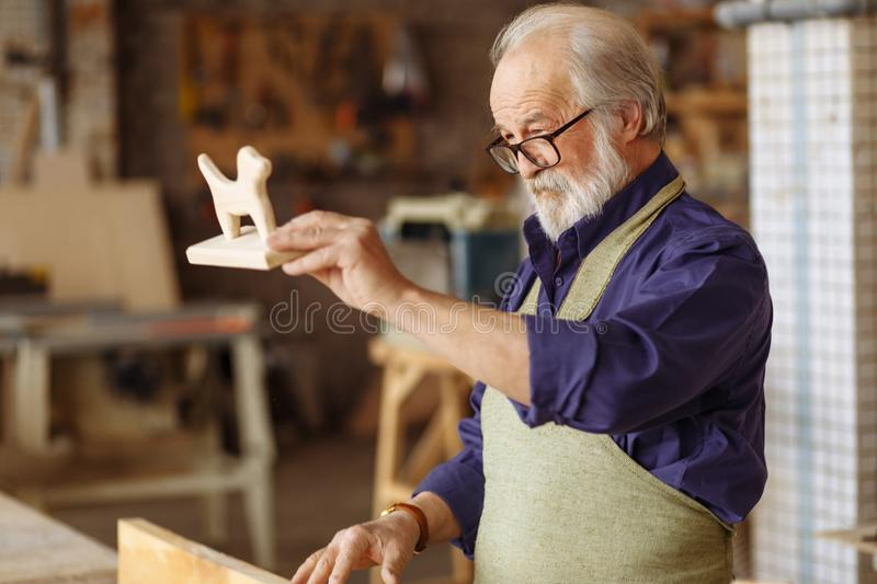 Old carpenter has finished making wood toy. Checking the ready good. creative wooden dog stock image