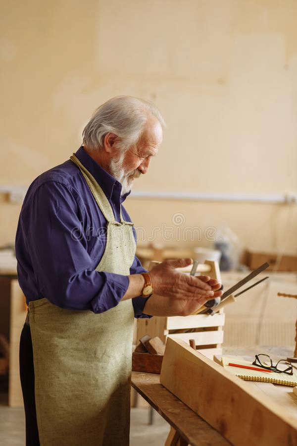 Old carpenter is rubbing his hands together after finishing work royalty free stock photo