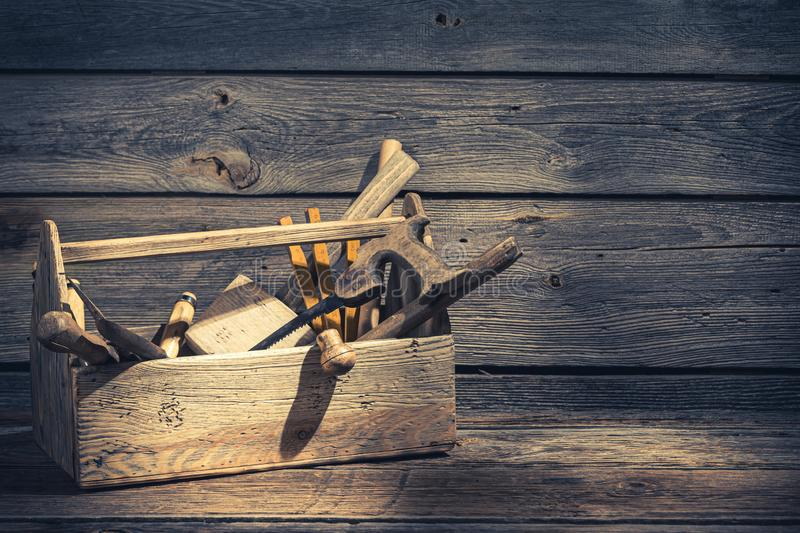 Old carpenters tool box in rustic wooden shed. On wooden table stock images