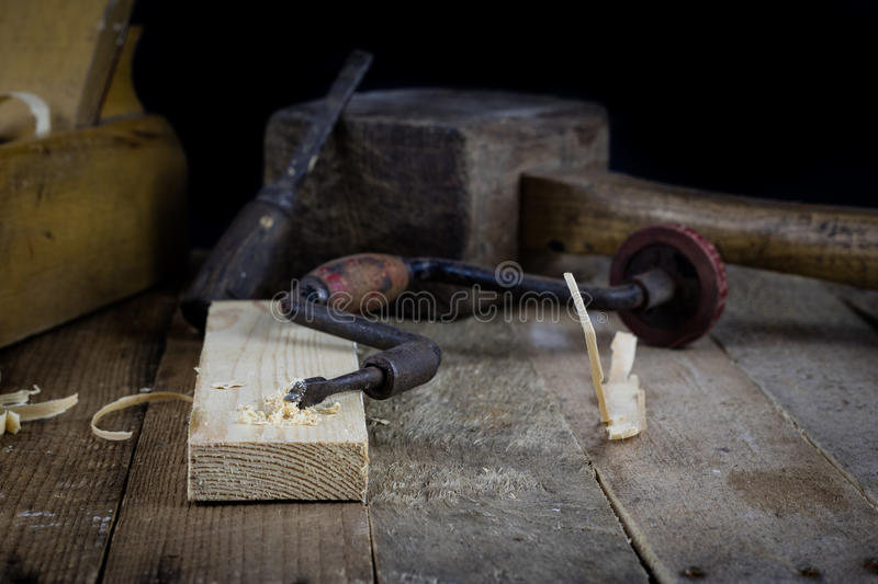 Old carpentry. Great passion, wonderful job. Old carpentry works. Old carpentry, carpentry workshop, drilling in a piece of wood royalty free stock photography