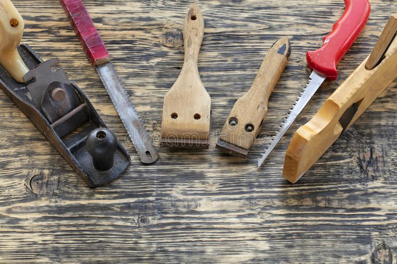 Old carpentry tools lie on a wooden table. Old carpentry tools, planers, handsaws and cycles lie on a wooden table royalty free stock image
