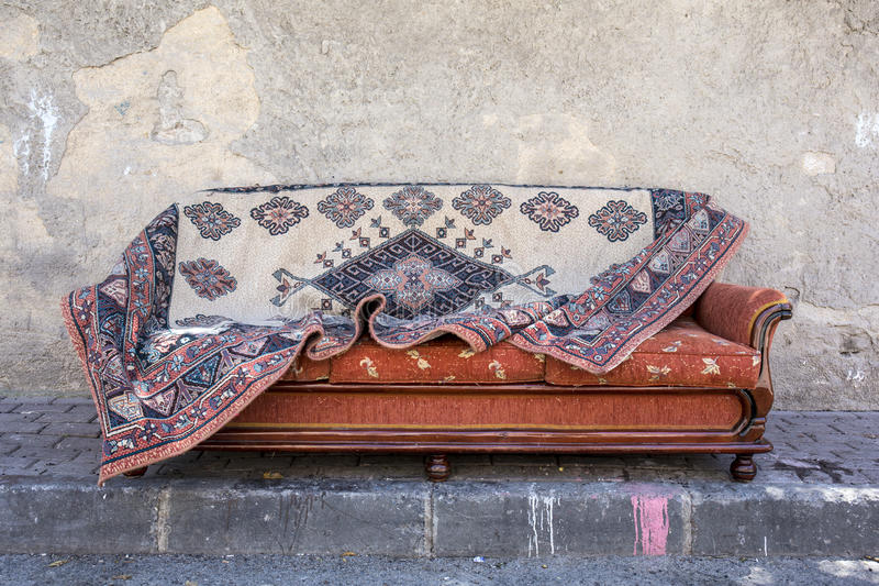 Old carpet on sofa bed. Infront of wall royalty free stock image