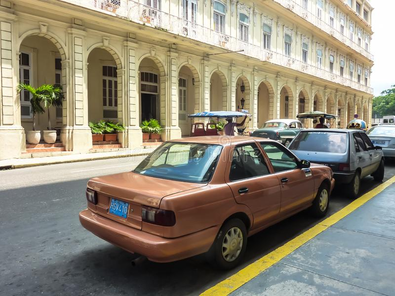 Old cars, standing near a footpath on the street of old Havana, Cuba royalty free stock photography