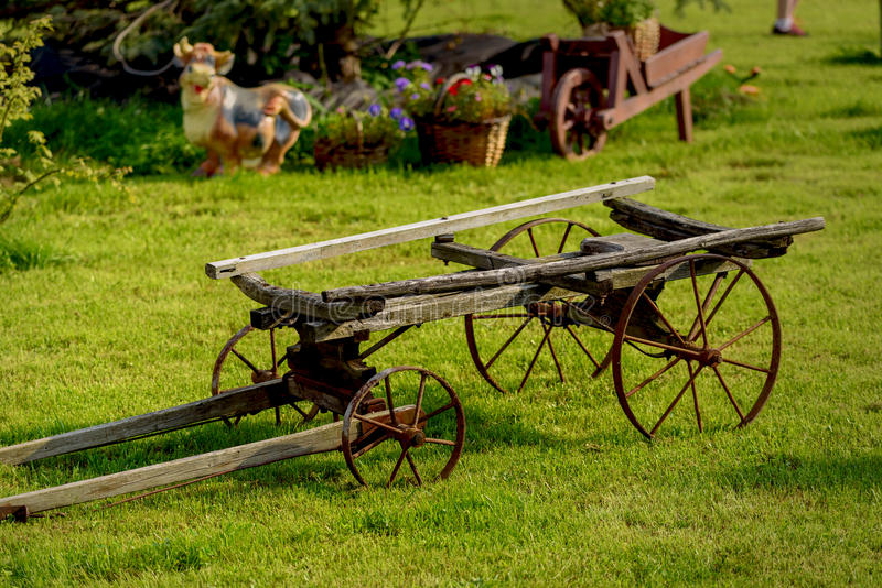 Old cart as a decorative element. On a green lawn royalty free stock image