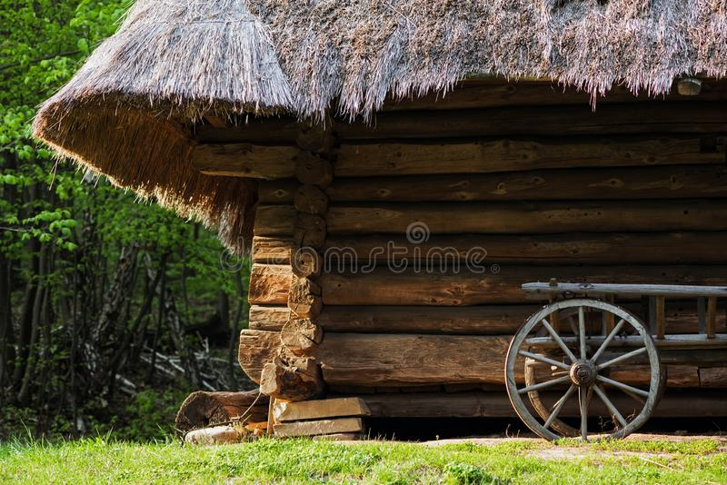 Old cart with wooden wheels against the background of a log house under thatched roof royalty free stock photos