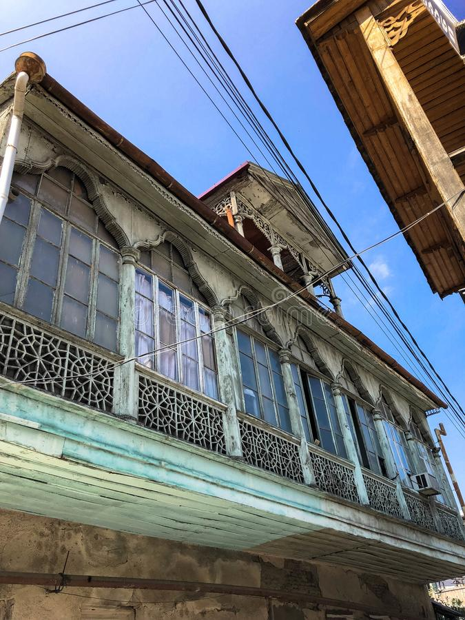 Old carved beautiful antique balcony of a wooden european house. European old architecture. Vertical photo royalty free stock photography