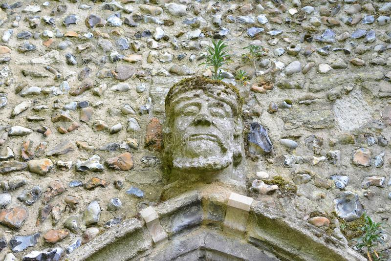 Old stone face. An old carved stone face on a cathedral church wall in Bury St Edmunds stock images