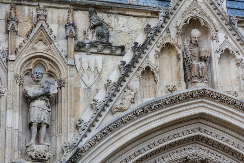 Stone statues carved on a cathedral wall. Old carved stone statues over the door to York cathedral stock images