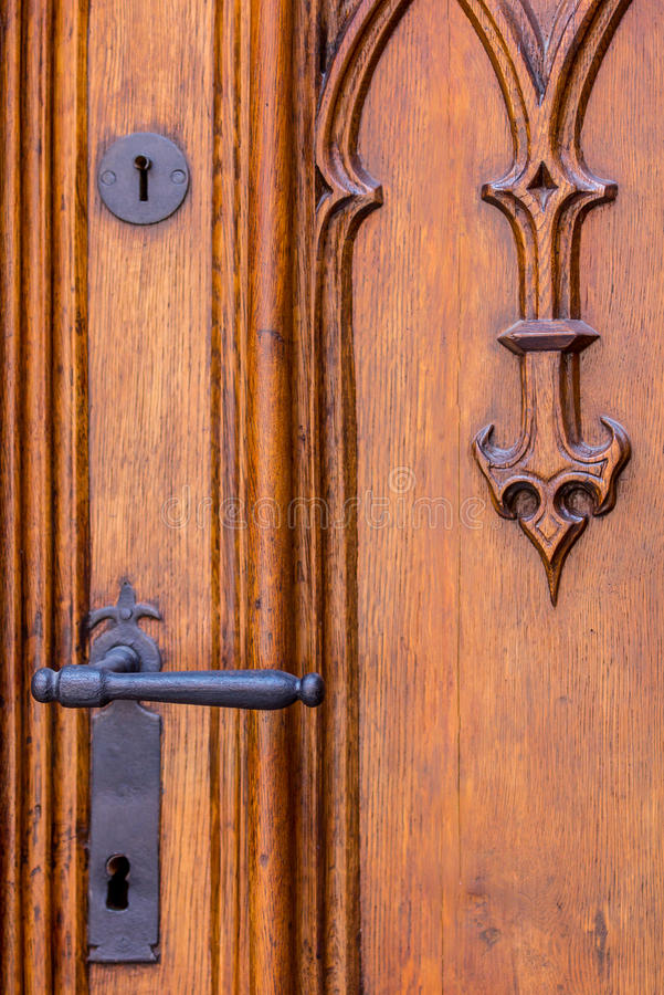 Old carved wooden door- close-up. Details of old carved wooden door, brass, metal handle, fittings. Jagiellonian University-Collegium Maius-Cracow (Krakow) stock photo