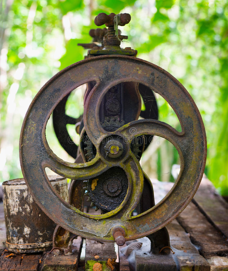 Old cast iron machine for squeezing the latex royalty free stock photo