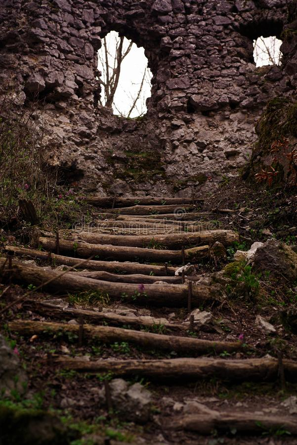 Old castle. Path leading to the old castle.the wall of an old stone castle and in front of it a wooden staircase leading upwards stock photo