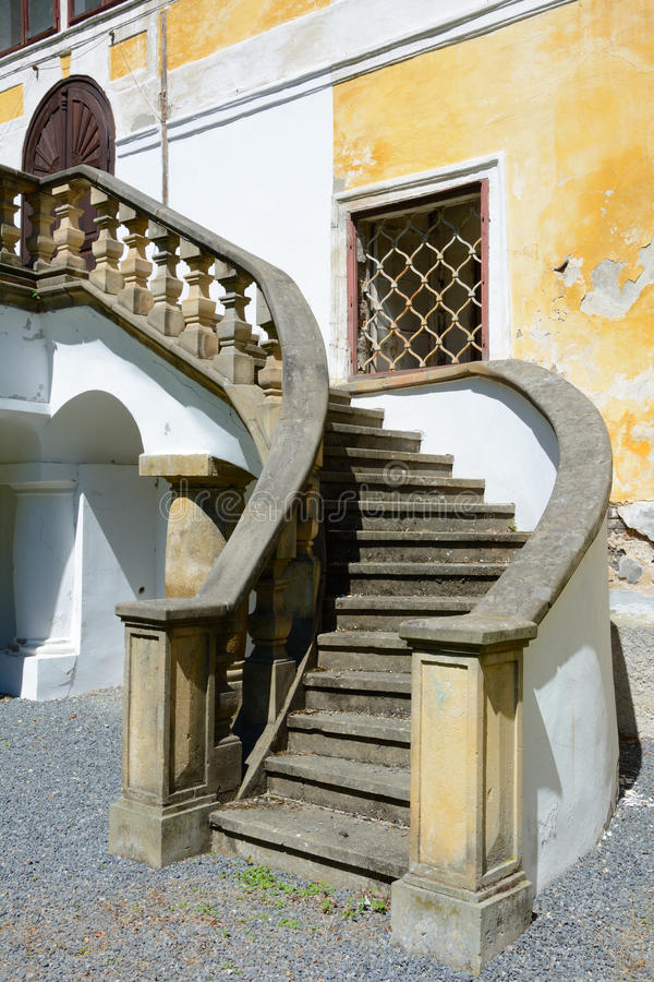 Old castle stairs. Stone stairs leading to the palace balcony of the old castle in ChotÄ›boÅ™. Open window with window bars visible. Falling stucco on the stock photo