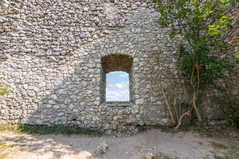 Old castle window with tree near stone. Clouds inside the window. royalty free stock image