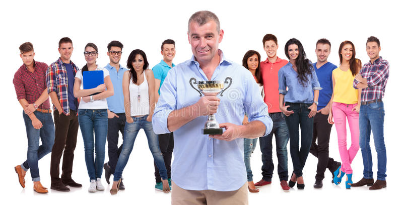 Old casual man holding a trophy cup in front of winning team stock image