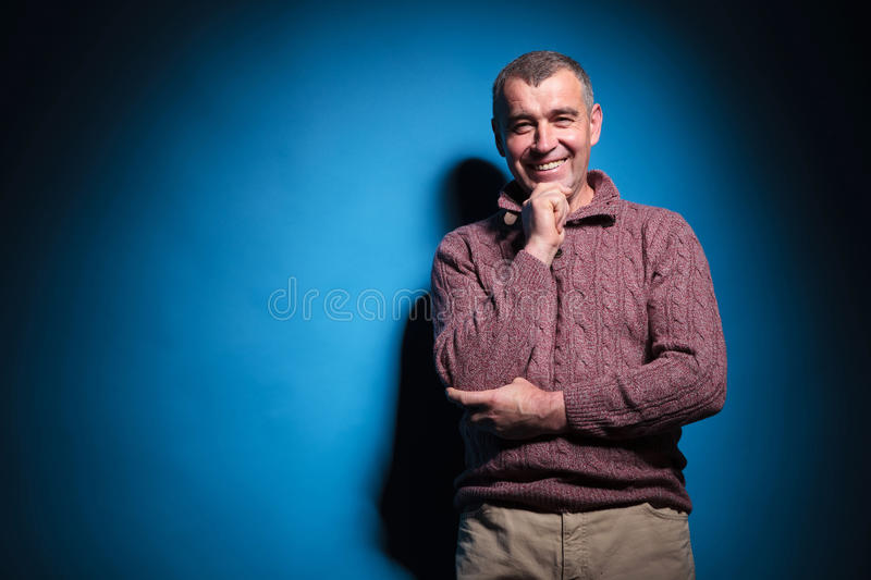 Old casual man smiles with hand on chin. Closeup portrait of a casual senior man smiling into the camera while holding a hand on his chin. on a blue vignetted stock photos