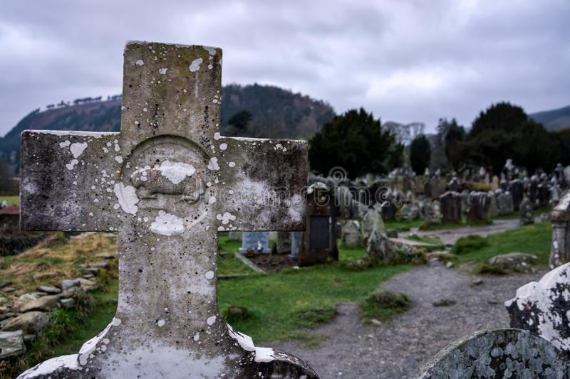 Old catholic granite cross on tombstone with cemetery and tombstones in background, Glendalough, Ireland stock photography