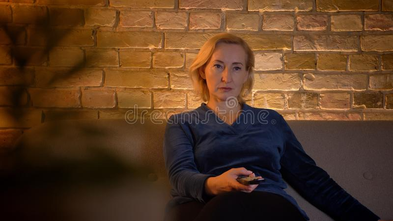 Old caucasian lady sitting on sofa and switching programmes on TV using remote controller in cozy home atmosphere. stock photo