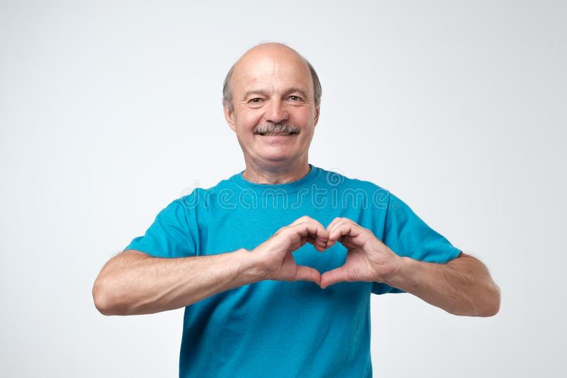 Old caucasian man in blue t-shirt making out of hands heart. Doing charity work, take care of the health, or being in love stock photos