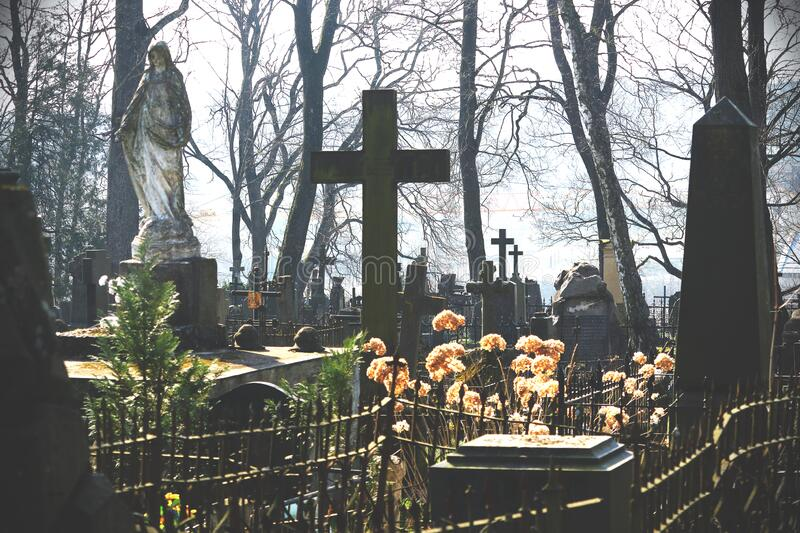 Old cemetery with grave stones and crosses in spring. Bright sun stock images