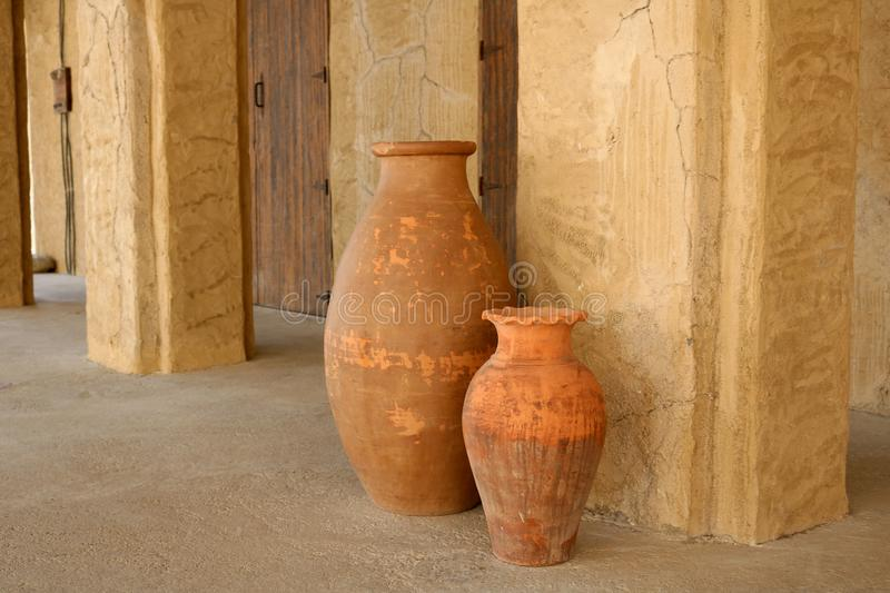 Old ceramic jugs. Vintage Arabian water jugs next to the wall stock image
