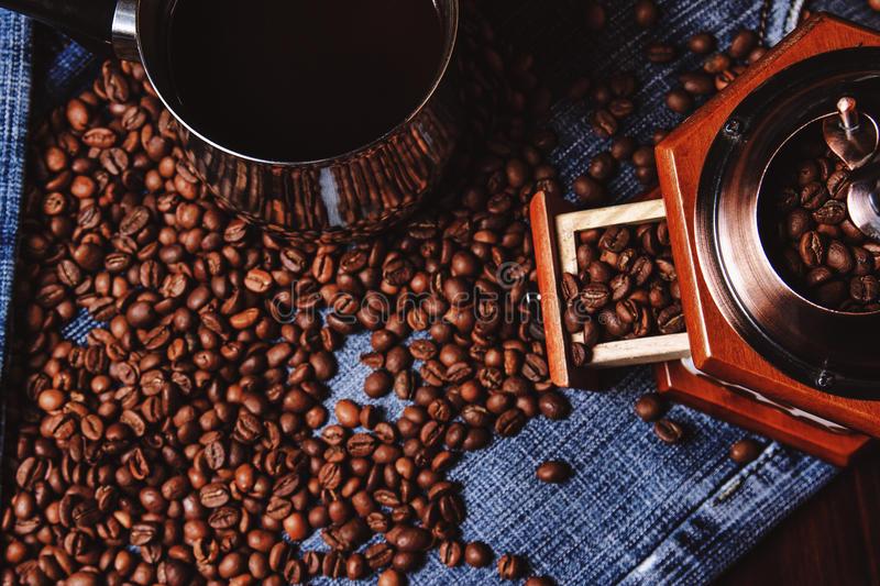 Old cezve, coffee grinder and black coffee beans royalty free stock images