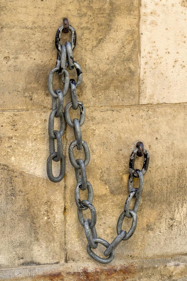 Old chain on the facade of a stone house.  stock image