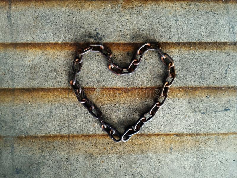 Old chain heart-shaped. On cement floor for background stock image