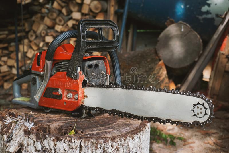 A old chainsaw set on a trunk in the barn stock image