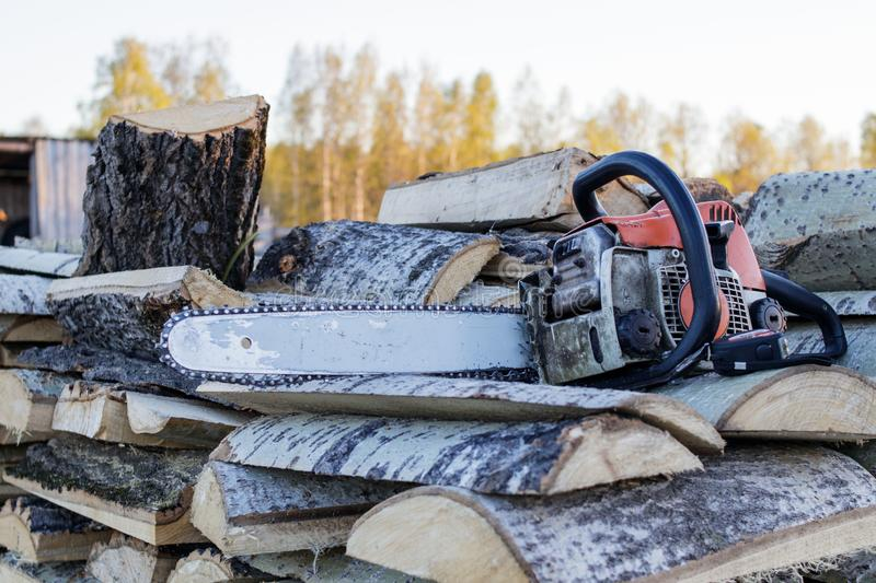 Old chainsaw and tape measure lying on a woodpile of aspen firewood royalty free stock photos