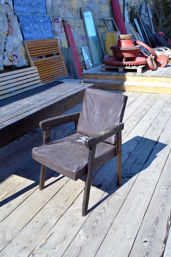 Old chair covered in artificial leather on a wooden deck stock photography