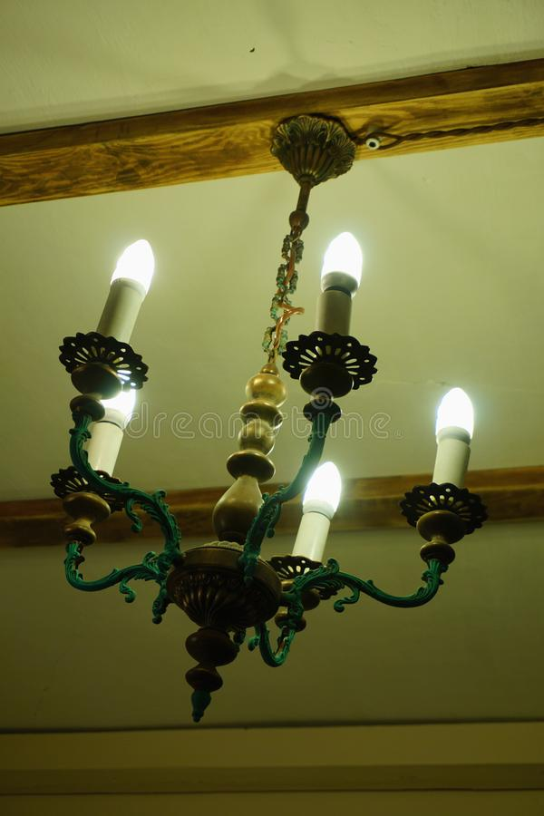 Old chandelier with five lamps hangs on the ceiling with a pre-revolutionary house. stock photos