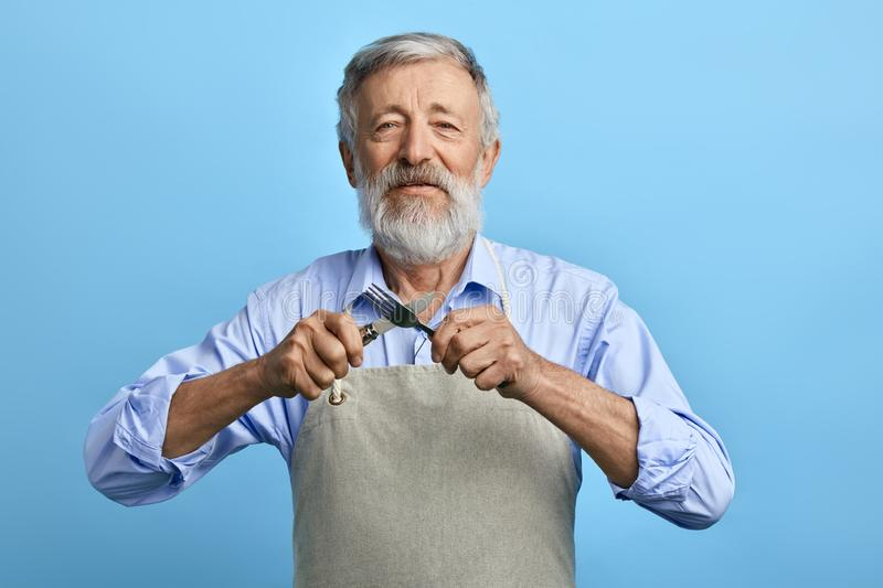 Old cheerful chef or waiter in gray apron, blue shirt holding fork, spoon royalty free stock photography