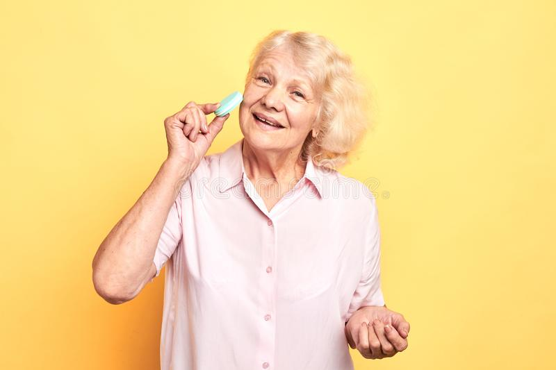 Old cheerful happy woman touching her face skin with sponge, royalty free stock image