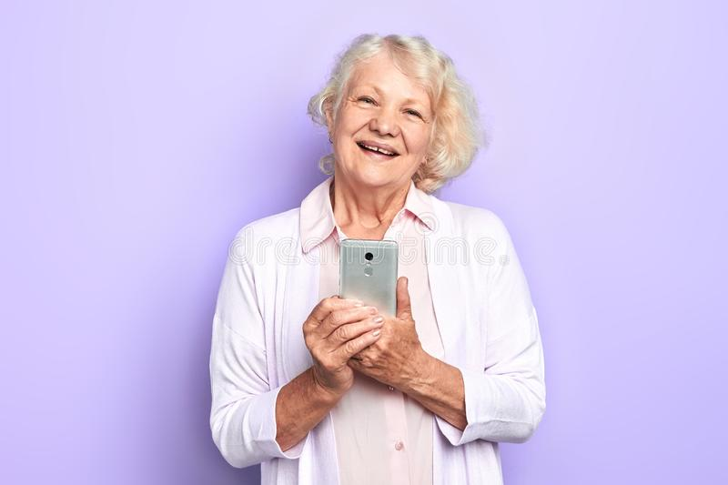 Old cheerful happy woman using her smartphone, isolated light blue background stock photos