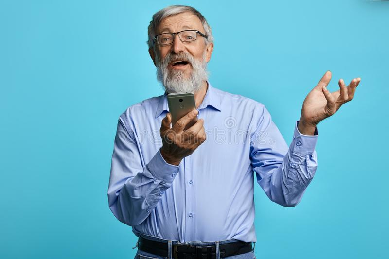 Old cheerful man with raised hand holding mobile phone royalty free stock photos