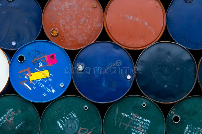 Old chemical barrels. Blue, green, orange oil drum. Steel oil tank. Toxic waste warehouse. Hazard chemical barrel with warning. Label. Industrial waste in metal stock photography