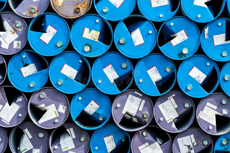 Old chemical barrels. Blue and purple oil drum. Steel oil tank. Toxic waste warehouse. Hazard chemical barrel with warning label. royalty free stock image