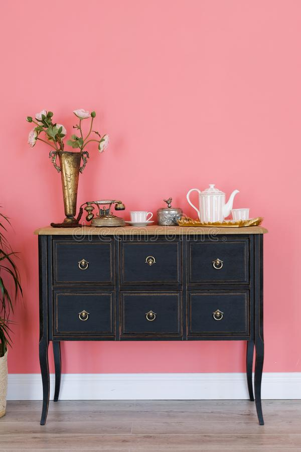 Old chest of drawers isolated on pink wall background . Next is a flower in a pot. Beautiful interior stock photo