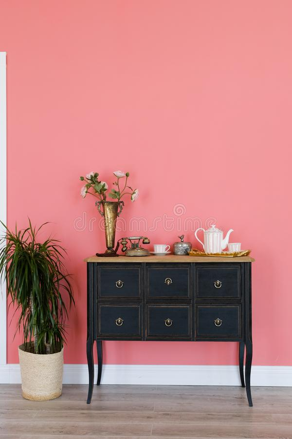Old chest of drawers with objects on the background of a pink wall. Next is a flower in a pot. Beautiful interior stock image