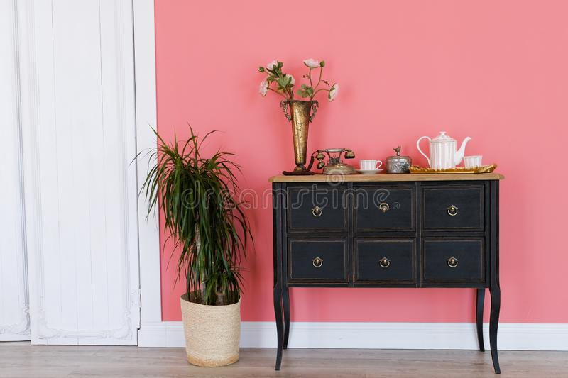 Old chest of drawers with objects on the background of a pink wall. Next flower in a pot, white door. Beautiful interior royalty free stock photos