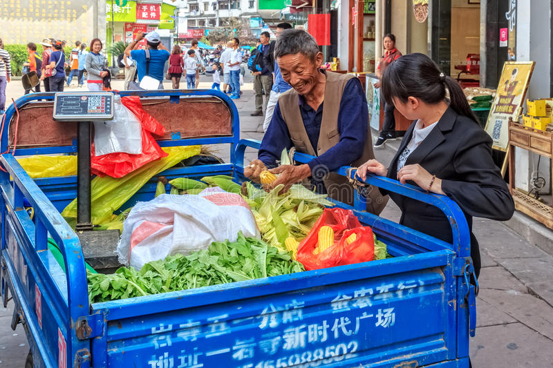The old Chinese farmer sells fresh corn and vegetables in China royalty free stock images