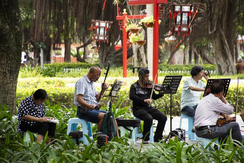 Old chinese people meet friends and sing song with playing classic musical instruments concert in park at Guangdong, China. Old chinese people meet friends and stock images
