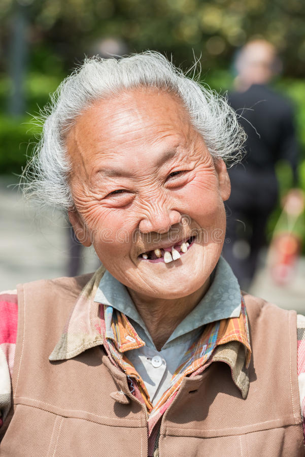 Old chinese woman friendly toothless toothy smiling outddors por