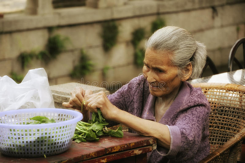 Old Chinese Woman. An old chinese woman sitting at a table tearing spinach leaves into smaller pieces at Tongli town Jiangsu province China