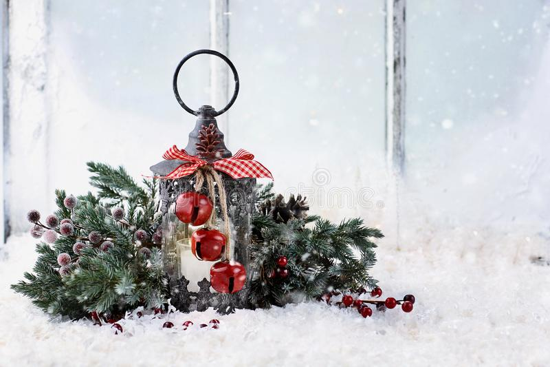 Old lantern on window ledge. Old Christmas lantern with pine tree branches sitting on a snowy window ledge royalty free stock images