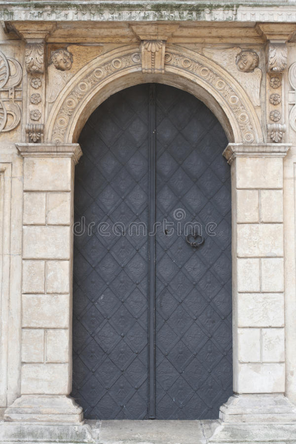 Old church textured door with stone arch facade. Krakow stock photo