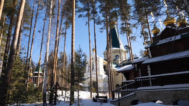 Old church tilt with white trees on hill in Russian winter season. Temple in the forest in winter royalty free stock photography